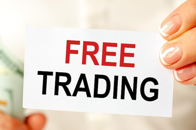 Auf dem tisch liegen rechnungen, ein bündel dollar und ein schild, auf dem es steht - freier handel. geschäfts-, marketing- und werbekonzept.