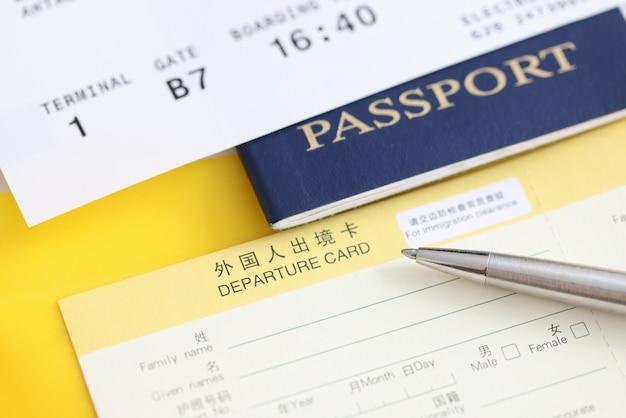Auf dem tisch liegen reisepass, ticket und abflugformular. umzug in ein anderes länderkonzept