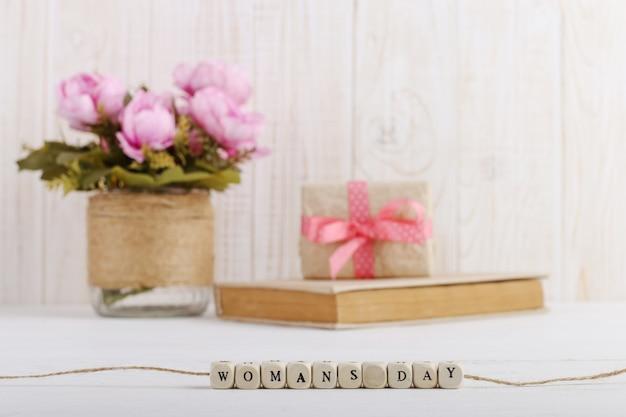 Auf dem tisch liegen rosa blumen in einer vase, ein buch und ein geschenk