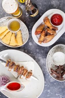 Auf dem tisch liegen saftiger schaschlik und verbrannte hähnchenschenkel mit würziger tomatensauce, croutons und gebratenem käse in semmelbröseln und einem gefüllten glas bier