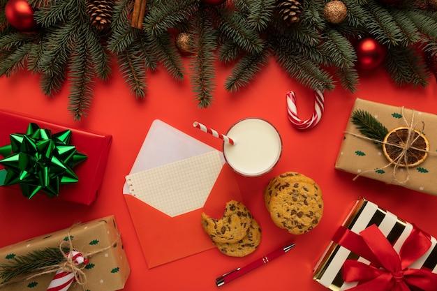 Auf dem tisch liegt ein umschlag mit einem brief sowie kekse und milch für den weihnachtsmann.
