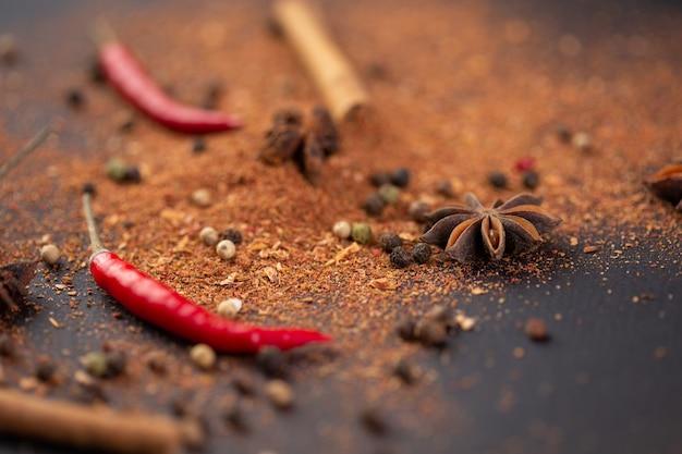 Auf dem tisch liegt eine nahaufnahme von würzigem rotem paprika-zimt und gemahlenem pfeffer.