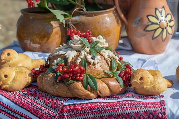 Auf dem tisch liegt neben dem bestickten handtuch ukrainisch dekorierter frischer laib mit salz. ukrainische und russische hochzeitstraditionen. leckerer kuchen, nahaufnahme