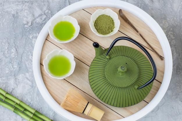 Auf dem tisch matcha tee in tränkeschüsseln, teebesen, löffel, bambus und teekanne