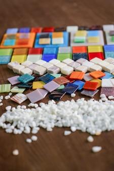 Auf dem tisch sind schöne farbige mosaikfliesen sortiert