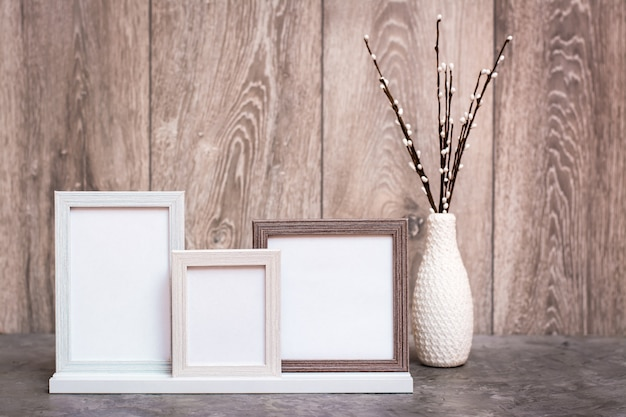 Auf dem tisch stehen drei leere bilderrahmen und eine vase mit künstlichen weidenzweigen. weiß-grau-beige farbskala. kopieren sie platz