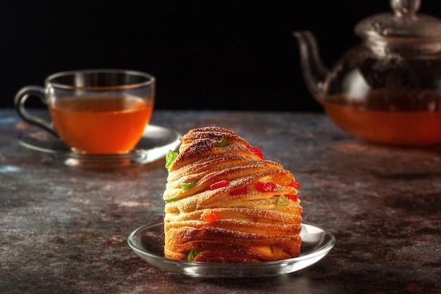 Auf dem tisch stehen kraffine mit rosinen, kandierten früchten und mohn, bestreut mit puderzucker.