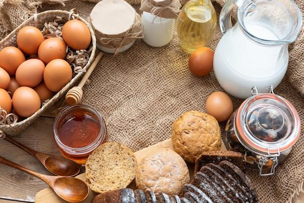 Auf dem tisch stehen natürliche hausgemachte produkte. milch, hühnereier, honig und sauerrahm.