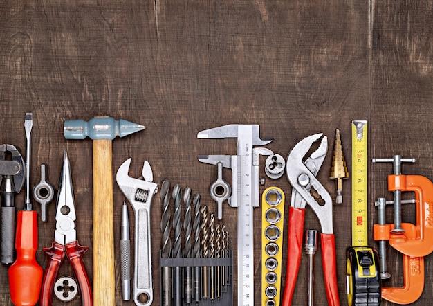 Auf dem tisch stehen werkzeuge für verschiedene bau- und reparaturarbeiten an holz, metall, beton, kunststoff und anderen materialien.