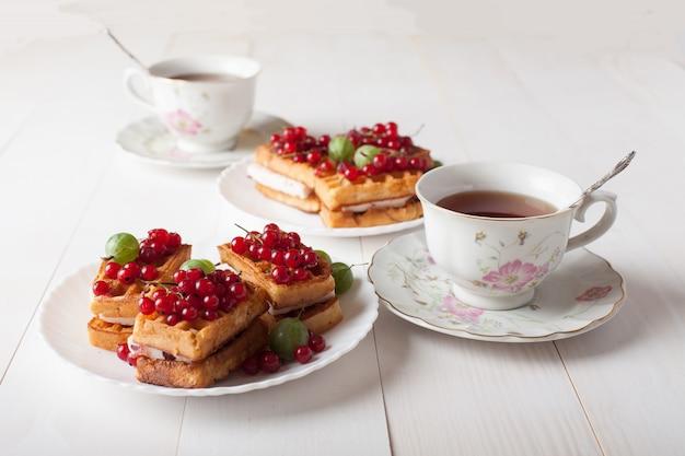 Auf dem tisch stehen wiener waffeln mit beeren und einer tasse tee