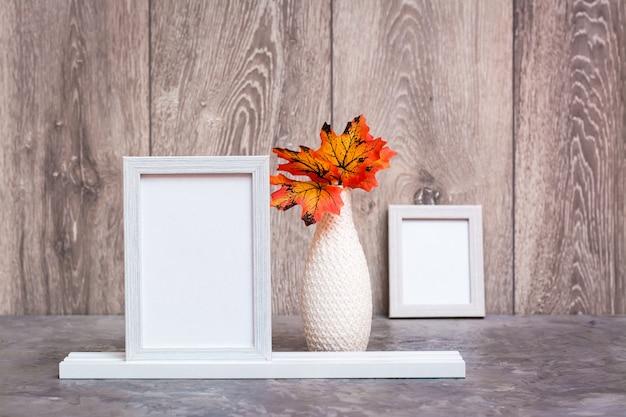 Auf dem tisch stehen zwei leere bilderrahmen auf einem ständer und eine vase mit orangefarbenen ahornblättern. weiß-orange-beige-farbschema. kopieren sie platz