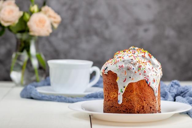 Auf dem tisch steht ein frisch gebackener osterkuchen mit einer tasse tee im hintergrund