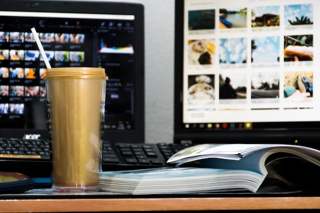 Auf dem tisch steht ein goldener becher und daneben ein buch. und im hintergrund ist es ein notebook und ein computermonitor.
