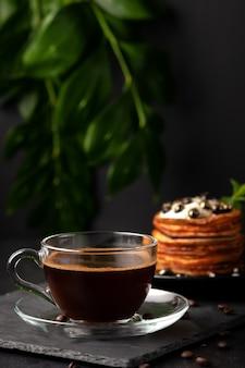 Auf dem tisch steht eine tasse frisch gebrühten duftenden kaffees mit hausgemachten pfannkuchen mit frischen beeren