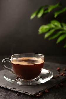 Auf dem tisch steht eine tasse frisch gebrühten, duftenden schwarzen kaffee