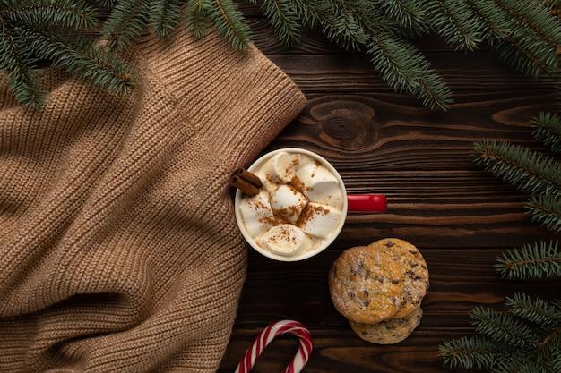 Auf dem tisch steht eine tasse heiße schokolade mit marshmallows und hausgemachten keksen mit weihnachtsdekoration.