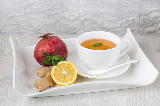 Auf dem tisch tee in einer tasse, ingwer, zitrone, minze und granatapfel auf einem tablett. freier platz für text