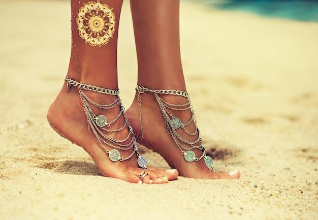 Auf dem tropischen sand stehen füße von frauen auf zehenspitzen, die mit schmuck im boho-stil bedeckt sind. gebräunte, gut gepflegte frauenfüße mit weißer pediküre, verziert mit stilvollen boho-armbändern mit ketten