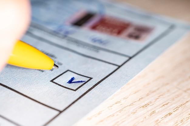 Auf dem wahlschein im quadrat markieren. wahl einer politischen partei, über die abgestimmt werden soll. markierung in der auswahl und einen nahaufnahmestift. präsidentschafts- oder parlamentswahlen im land. konzept der wahl.
