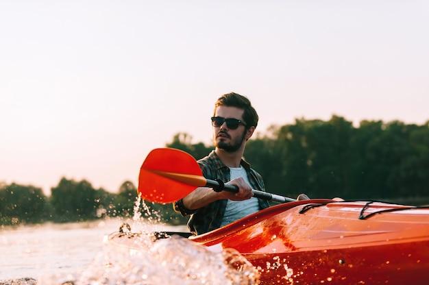 Auf dem wasser sicher fühlen. selbstbewusster junger mann beim kajakfahren auf dem see mit sonnenuntergang im hintergrund