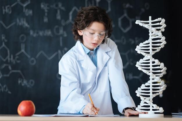 Auf dem weg zu erfindungen. begabtes kluges, aufmerksames kind, das im labor steht und das genetische codemodell studiert, während es am wissenschaftsprojekt arbeitet und sich notizen macht