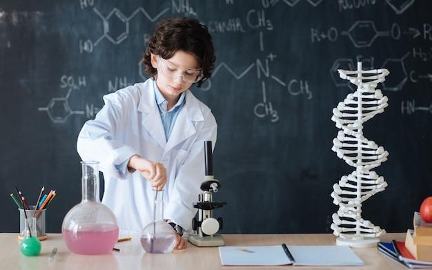 Auf dem weg zum erfolg. aufmerksamer, talentierter, intelligenter forscher, der im labor steht und während der teilnahme am experiment den mikrobiologieunterricht genießt