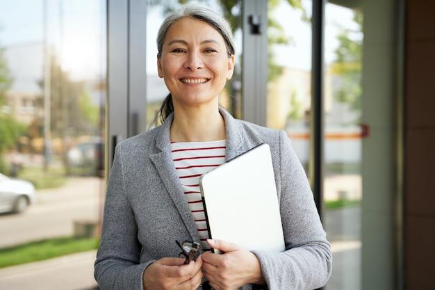 Auf dem weg zur arbeit. vertikale aufnahme einer schönen und glücklichen seniorin, geschäftsfrau, die laptop hält und in die kamera lächelt, während sie in der nähe des bürogebäudes steht. geschäftsleute, arbeitskonzept