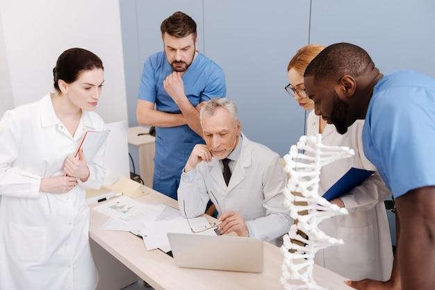 Auf dem weg zur erfindung. beteiligte intelligente junge praktikanten, die die klasse an der medizinischen hochschule studieren und genießen, während sie berichte an den alten professor weitergeben