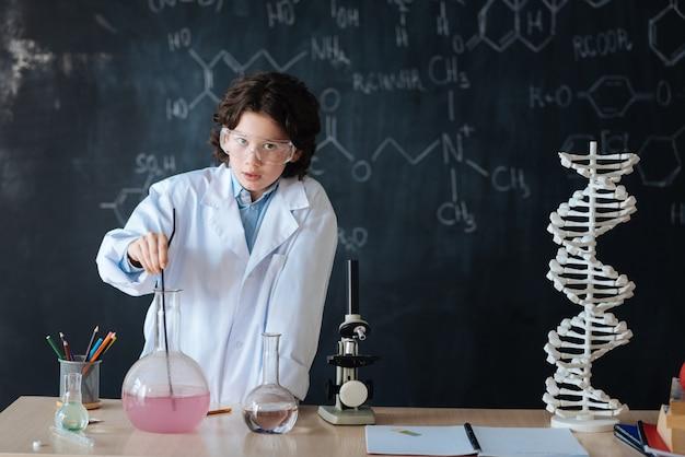 Auf dem weg zur erfindung. charmanter talentierter, geschickter forscher, der im labor steht und während der durchführung des experiments mikrobiologieunterricht genießt