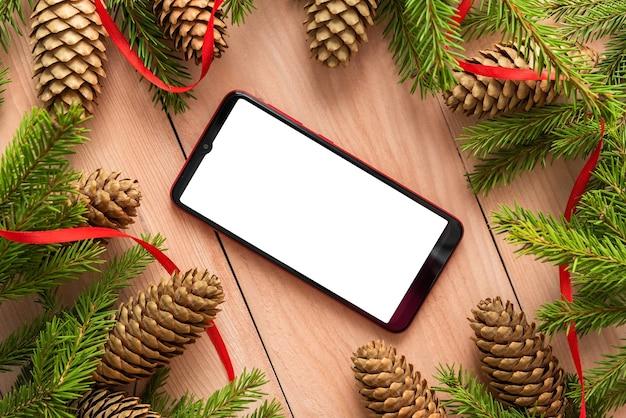 Auf dem weihnachtstisch stehen ein telefon und tannenzapfen mit zweigen.