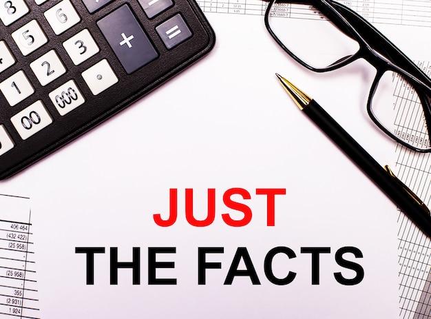 Auf den berichten befinden sich ein taschenrechner, eine brille, ein stift und ein notizbuch mit der aufschrift just the facts