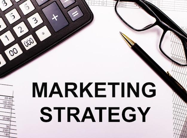 Auf den berichten befinden sich ein taschenrechner, eine brille, ein stift und ein notizbuch mit der aufschrift marketing strategy