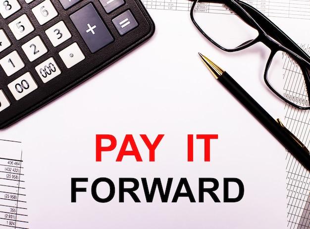 Auf den berichten befinden sich ein taschenrechner, eine brille, ein stift und ein notizbuch mit der aufschrift pay it forward