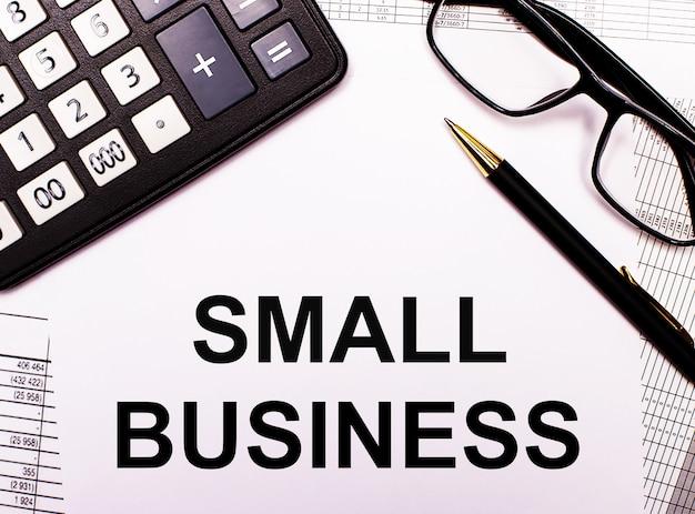 Auf den berichten befinden sich ein taschenrechner, eine brille, ein stift und ein notizbuch mit der aufschrift small business