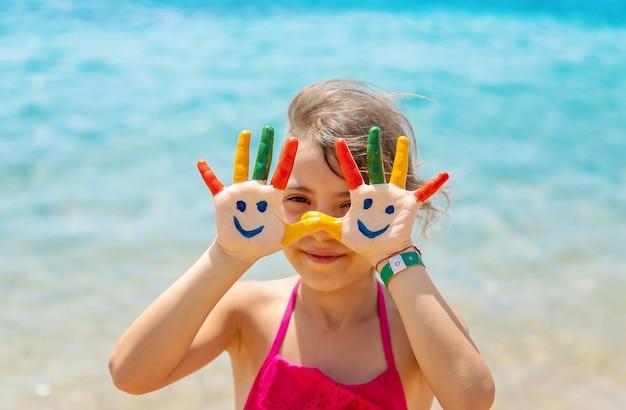 Auf den händen des kindes ein lächeln mit farben auf dem meer