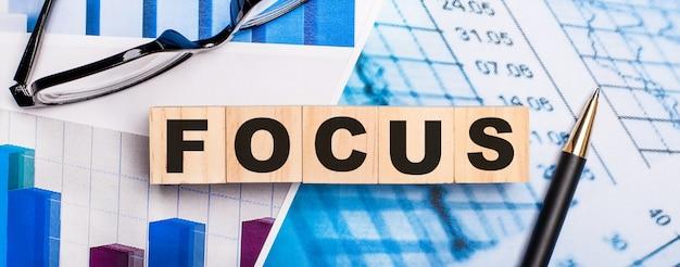 Auf den hellen diagrammen stehen brillen, ein stift und holzwürfel mit dem wort focus