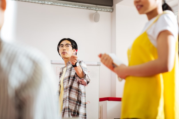 Auf den lautsprecher zeigen. ruhige erfahrene lehrerin, die ein seminar leitet und auf die sprecherin zeigt, während sie sie ansieht