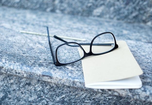 Auf den stufen eines bürogebäudes liegen eine brille und ein notizbuch mit einem stift.