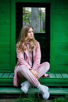 Auf den stufen sitzt eine junge frau mit blonden haaren europäischen aussehens. mädchen in rosa anzug und turnschuhen