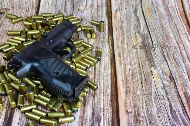Auf den verstreuten traumatischen patronen liegt eine pistole auf einem hölzernen hintergrund. rechts ist ein leerer platz zum einfügen eines etiketts