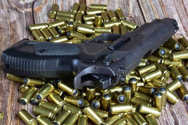 Auf den verstreuten traumatischen patronen liegt eine schwarze pistole. zusammen liegen sie auf braunen holzbrettern
