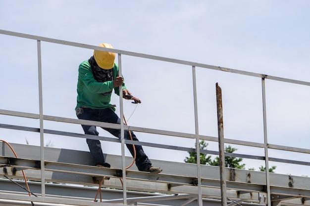 Auf der baustelle arbeiten die schweißer bei der arbeit auf dem dach.