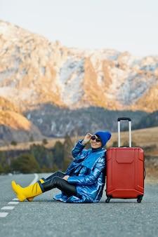 Auf der bergstraße sitzt eine frau in blauer jacke und hut und leuchtend gelben stiefeln mit einem roten koffer auf den bergstraßen