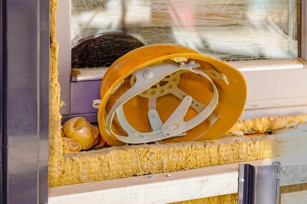 Auf der fensterbank des fensterrahmens liegt ein gelber schutzhelm zur sicherheit der arbeiter. mittagspause. rest der arbeiter.