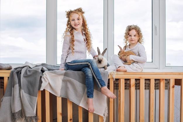 Auf der fensterbank sitzen zwei schöne kindermädchen mit lockigen haaren und flauschigen tierkaninchen