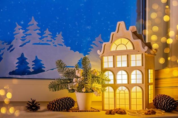 Auf der fensterbank, zwischen den christbaumschmuckstücken, leuchtet ein nachtlicht in form eines alten europäischen hauses in der nähe eines nachtschneefensters und von papierdekorationen.