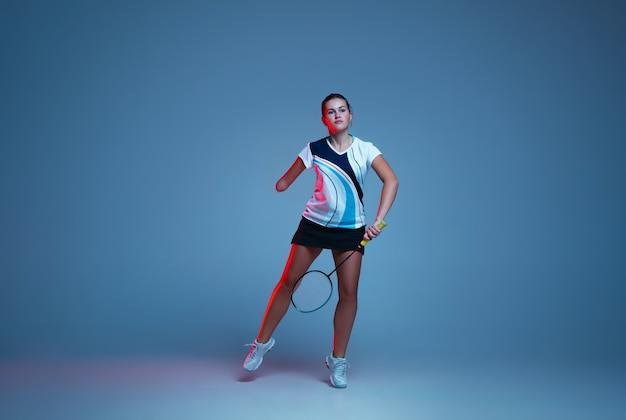 Auf der flucht schöne handicap-frau, die im badminton übt, isoliert auf blauem hintergrund