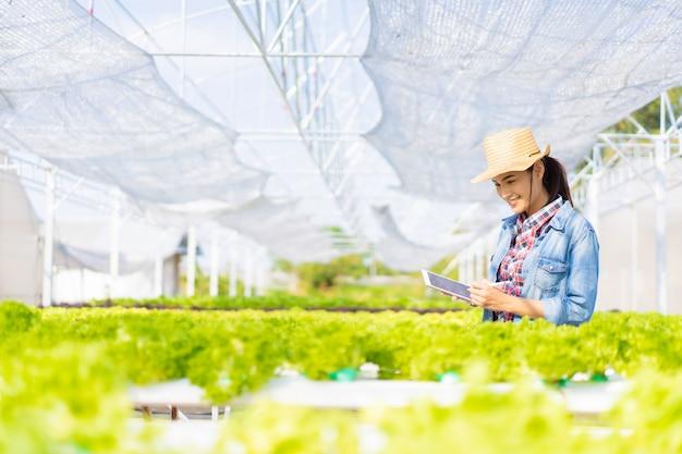 Auf der gemüsesalatfarm hydroponic zeichnen die landwirte daten auf tabletten auf.