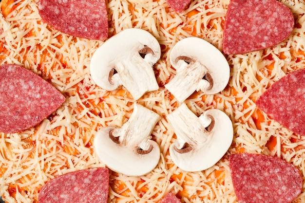 Auf der geriebenen käsepizza werden wurst und pilze ausgelegt
