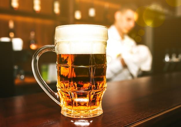 Auf der hölzernen bartheke steht ein glas bier mit schaum. alte kneipe mit barkeeper, der das geschirr im hintergrund säubert. freizeit, spaß und freunde konzeptfoto.
